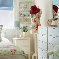 Pretty floral bedroom with dressmaker's mannequin and drawer storage