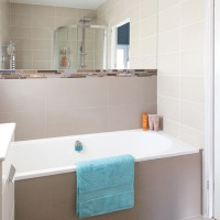 Smart neutral bathroom with wall to wall mirror and chrome fittings