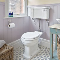 Period-style bathroom with lilac painted panelling and patterned floor tiles