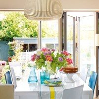 Bright dining room with bi-fold doors and view over garden
