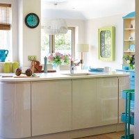Modern kitchen with curved hi-gloss units and blue accessories