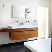 White bathroom with wooden vanity unit and tiled flooring