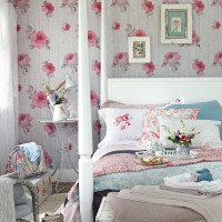 Pretty pink bedroom with four-poster bed and floral bed linen