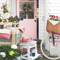 Cottage front garden with pink door and wicker baskets