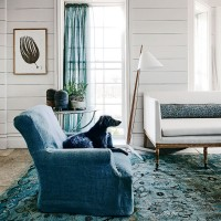 Pared-back living room with blue sofa and curtain