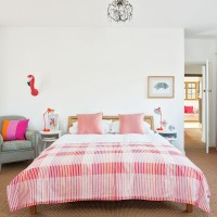 Pretty open-plan bedroom with sisal flooring and pink bedding