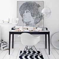 Black and white home office with iconic image and Eames chair