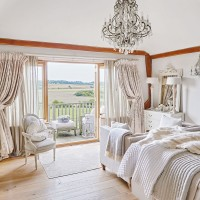 Grand neutral bedroom with a country view