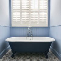 Traditional bathroom with blue roll top bath and shuttered windows