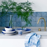 White kitchen with blue tiled splashback and fresh foliage
