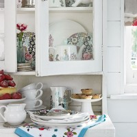 Vintage-inspired kitchen with white painted cabinetry and pretty china