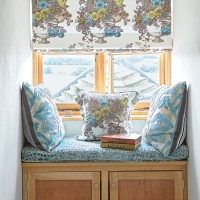 Bedroom window seat with blue patterned blind and seat cushions