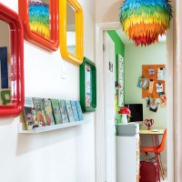 White landing area with colourful mirror and bookshelf display