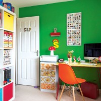 Home office with bright green feature wall and orange chair