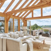 Spacious conservatory with wooden beams and neutral furniture
