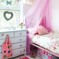 Girl's bedroom with pink bed curtain and floral bedding