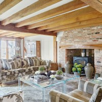 Period-style living room with wooden beams and brick fireplace
