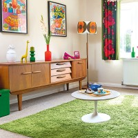 Retro living room with grass green rug and vintage prints