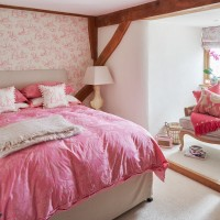 Country bedroom with candy pink bed linen and toile wallpaper