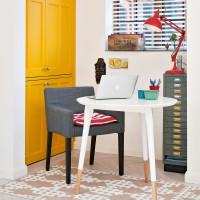 Colourful home office with yellow cupboards and armchair