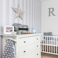 Grey nursery with striped wallpaper and white furniture
