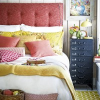 Country bedroom with berry coloured headboard