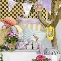 Garden seating area with patterned cushions and bunting