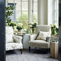 Pretty garden room with botanical print fabrics and potted plants
