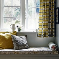 Bedroom window seat with retro yellow curtains and garden view