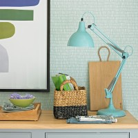 Pale mint home office with wooden desk and lamp