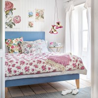 Modern country bedroom with floral bed linen and blue bedstead