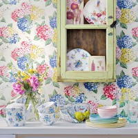 Shabby chic kitchen with distressed cabinet and floral wallpaper