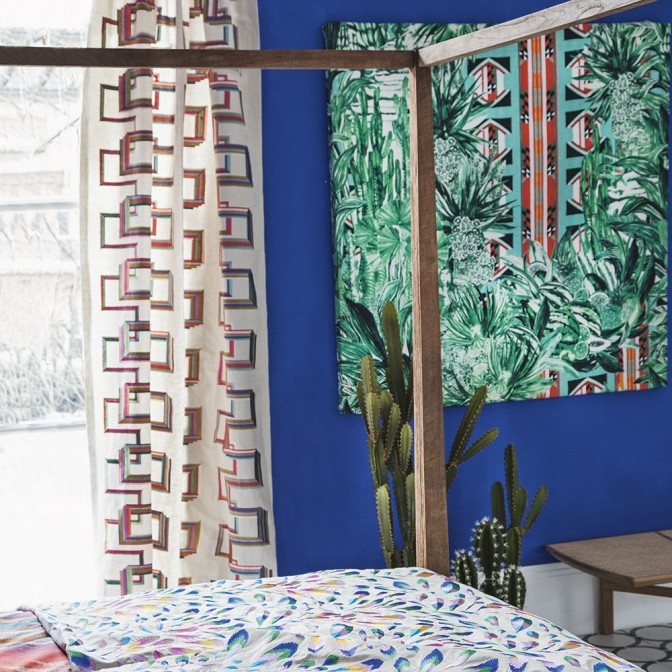 Bright blue bedroom with palm print wallpaper panel