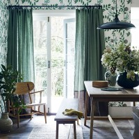 Modern country dining room with green curtains and botanical-style wallpaper