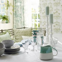 Classic dining room with ceramic tableware and botanical prints