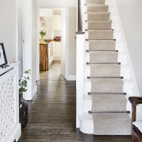White hallway with stripped floor and stair runner