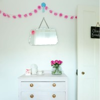 Simple white bedroom with pink accessories and retro touches