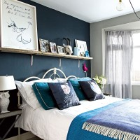 Deep blue bedroom with open shelving and feature cushions