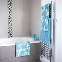 Grey tiled bathroom with mosaic details and aqua blue towels