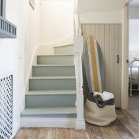 Modern hallway with pale blue stairs and surf board