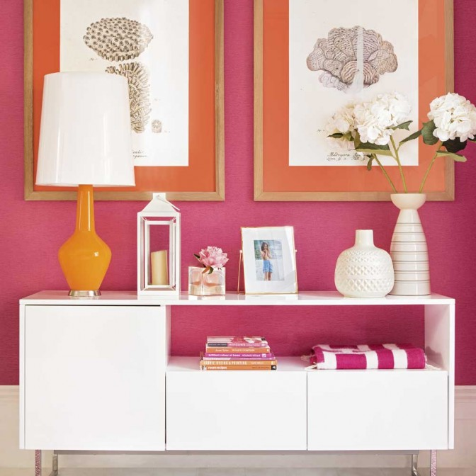 Hot pink and orange hallway with framed artwork and white sideboard