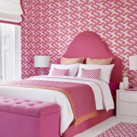 Hot pink bedroom with geometric wallpaper and ottoman