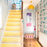 Bright hallway with painted staircase and graphic wallpaper