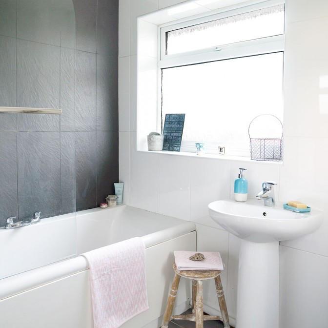 Black and white bathroom with slate wall and reclaimed stool