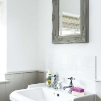 White walled bathroom with grey panelling and mirror