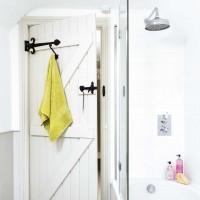 Plain white bathroom with farmhouse-style door