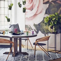 Botanical dining room with concrete table and rose mural