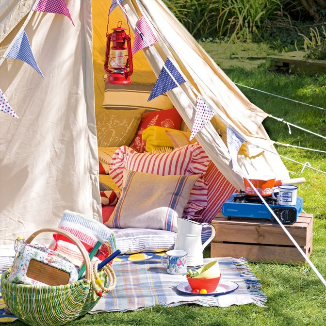 Garden with colourful camping accessories and tent