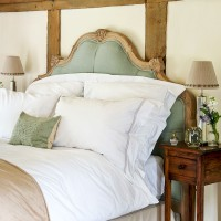 Country bedroom with carved upholstered bed