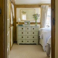 Beamed country bedroom with decorative chest of drawers